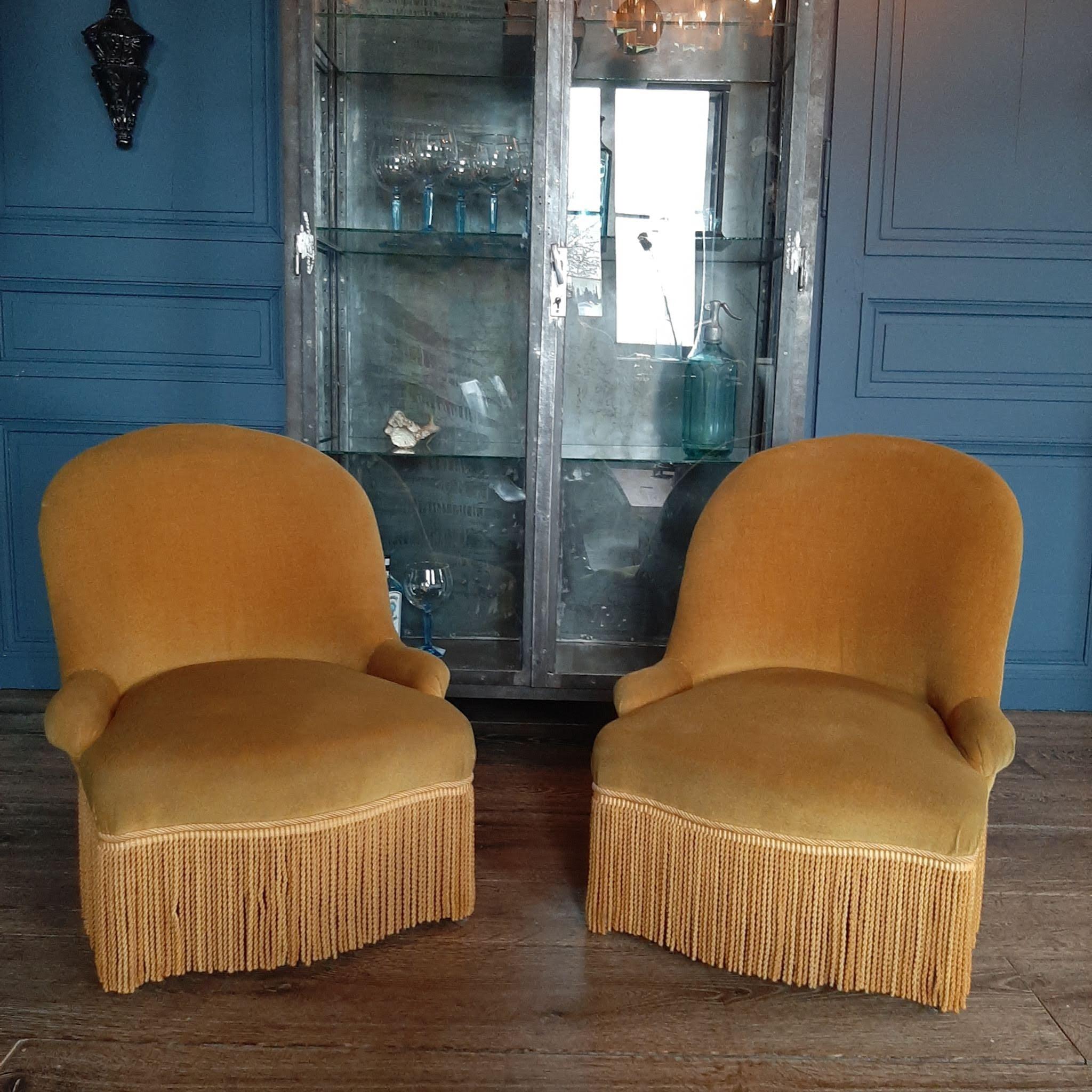 Ein Paar gelbe Samtstühle mit Fransen
