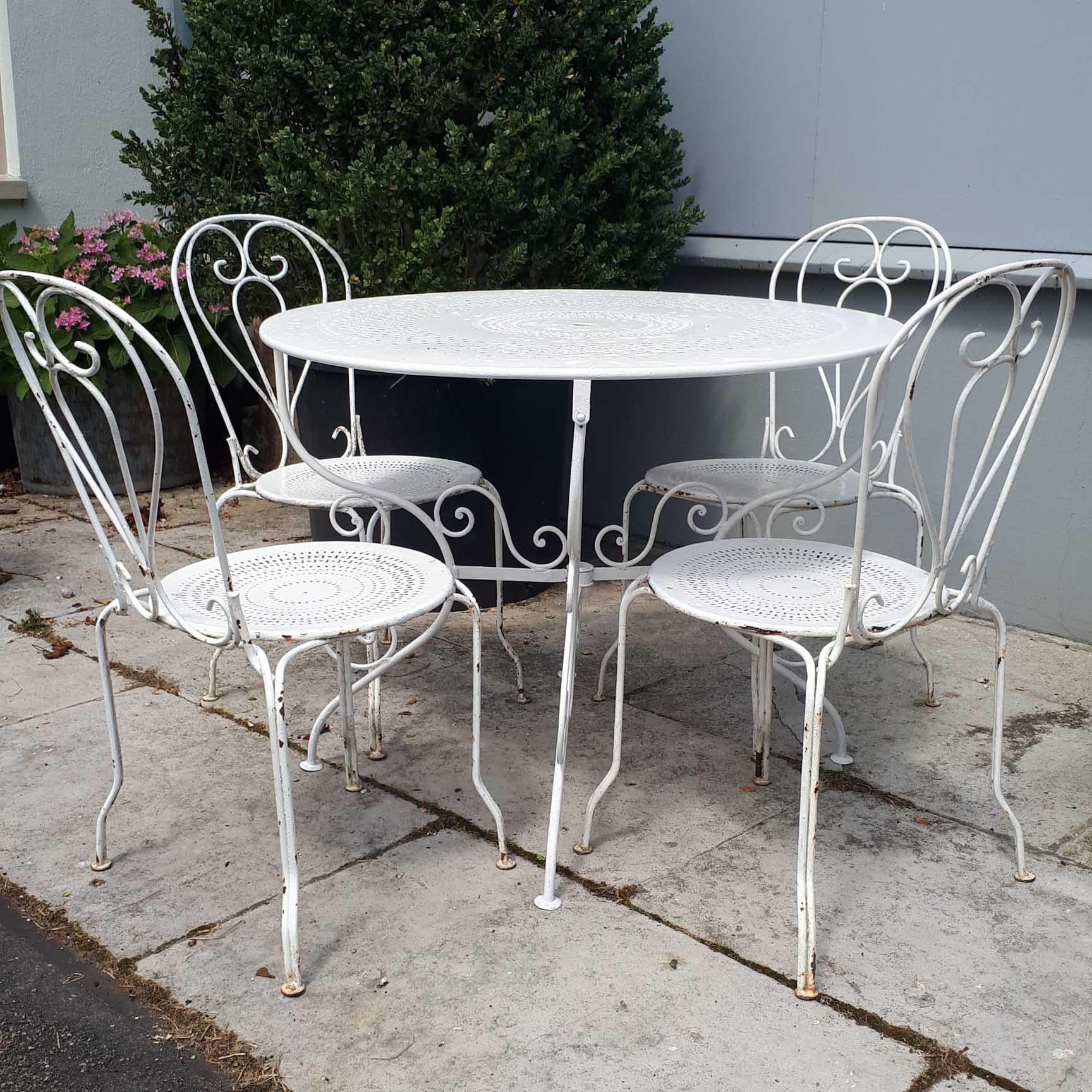 Alte Gartenmöbel, weißer Eisentisch mit vier Stühlen